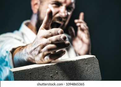 Karate fighter showing kick by hand. Karate man is preparing for competition. Screaming karate master instructor breaking with hand concrete brick. Selective focus on hand. Bearded man do training.