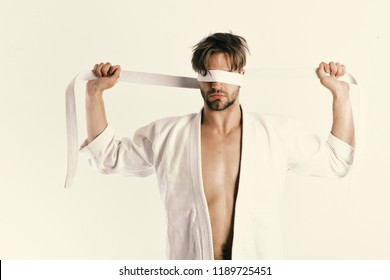 Karate fighter with strong body holds white belt. Man with hidden face and bristle isolated on white background. Healthy lifestyle and jujitsu concept. Guy posing in white kimono ties eyes with belt