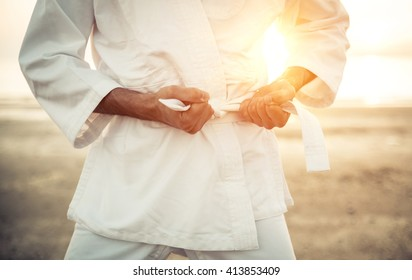 Karate fighter tying his kimono belt up, concept about martial arts