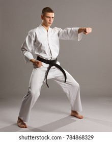 Karate in a fighting pose on the grey background.