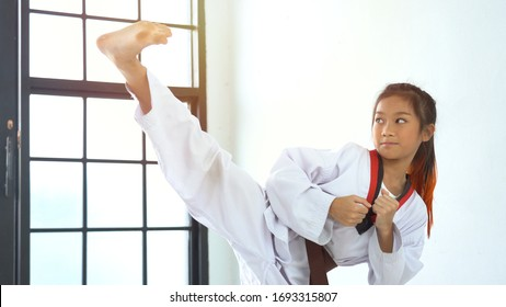 The karate girl with black belt in gym