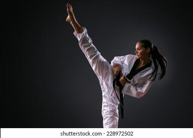 Karate girl with black belt posing on black background studio shot