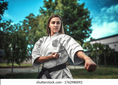 Karate girl with black belt training fist punch outside