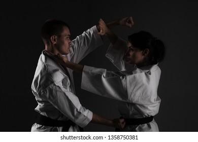 karate girl and boy fighting against dark background