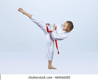 Karate girl with red belt is beating blow leg
