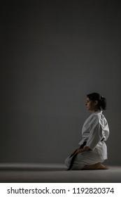 karate girl in a sitting pose against dark background