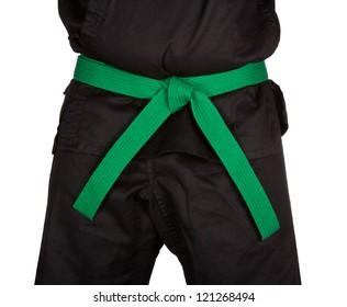 Karate green belt tied around marital artists torso wearing black dojo GI's.