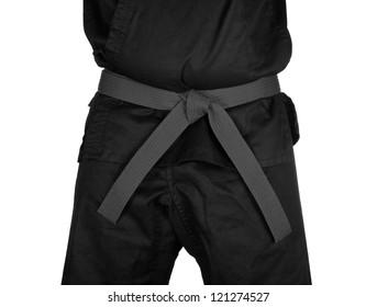 Karate grey belt tied around marital artists torso wearing black dojo GI's.