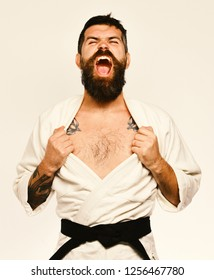 Karate man with angry face in uniform. Oriental sports concept. Taekwondo master with black belt tears his costume on chest. Man with beard in white kimono on white background.