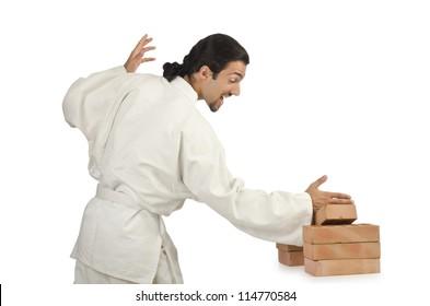 Karate man breaking bricks on white