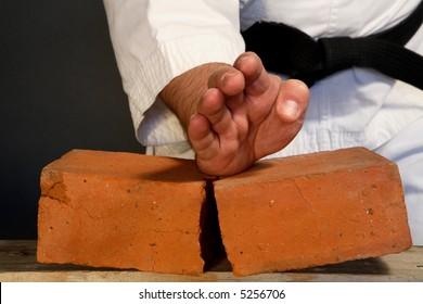 karate man breaking  bricks on gray background