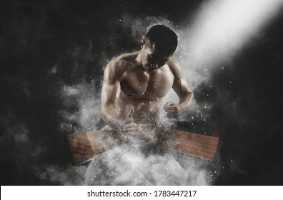 Karate man breaking with hand wooden board on smoke background. Sports banner. Horizontal copy space background