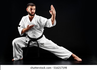 Karate man in a kimono in fighting stance on a black background