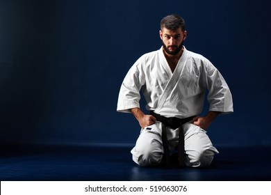 Karate man in a kimono sits on her knees on the floor on blue background
