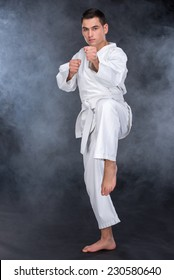 Karate martial arts. Fighter is looking at the camera, isolated on dark, foggy background.