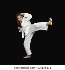 Karate practicing - little girl in sport white kimono with brave face beats foot on black background