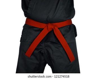 Karate red belt tied around marital artists torso wearing black dojo GI's.