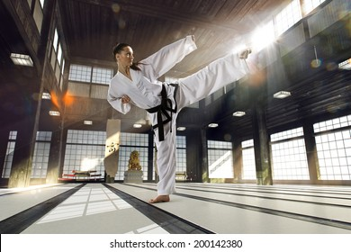 Karate woman in action on light  old sports hall