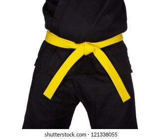 Karate yellow belt tied around marital artists torso wearing black dojo GI's.