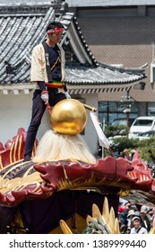 "Karatsu, Japan - may 5, 2019 : a man wearing traditional clothes on the top of a massive float during new imperial era ""reiwa"" celebration parade"