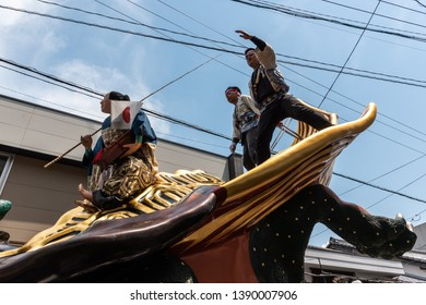 "Karatsu, Japan - may 5, 2019 : two men wearing traditional clothes on the top of a massive float during new imperial era ""reiwa"" celebration parade"