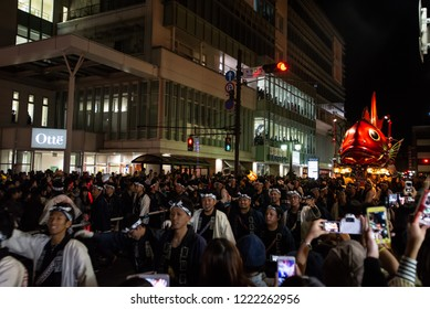 "Karatsu, Japan - november 2, 2018 : people in traditional costumes drawning a Sea bream shaped float through the street during ""kunchi"" Karatsu city annual parade at night"
