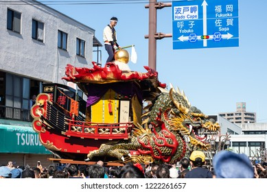 "Karatsu, Japan - november 3, 2018 : a men in traditional costumes is climbing on the Boat of seven treasures float while the float is drawning through the street during ""kunchi""  Karatsu city parade"