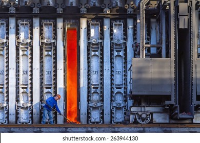 KARDEMIR, TURKEY - SEPTEMBER 6, 2013: Unknown worker cleans fallen coke from an open oven on the battery, Turkey on September 2013. Coke battery in Kardemir Karabuk Iron and Steel Industry and Trade