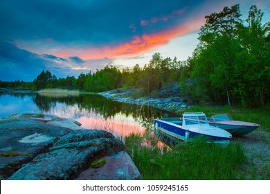 Karelia. Russia. Nature of Karelia. Water trips on Lake Ladoga. Rocky shore. Motor boats on the shore. Lake Ladoga on the background of sunset. The Republic of Karelia.