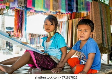 Karen Village near Pattaya, Thailand - January 21, 2017: Girl with a long neck weaves a headscarf and the boy is sitting near to her on January 21, 2017 in Karen Village near Pattaya, Thailand