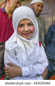 KARGIL, INDIA - JUNE 22: Unidentified muslim girl dressed in white hijab poses for a camera on June 22, 2016 in central market in Kargil, Jammu & Kashmir, Northern India.