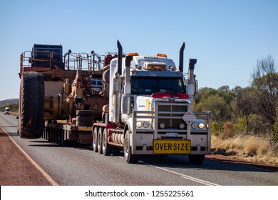 KARIJINI - WESTERN AUSTRALIA - JULY 11, 2018: The Western Star road train with Oversize sign and extremely wide dumper truck on an asphalt road in Western Australia near Karijini National Park.