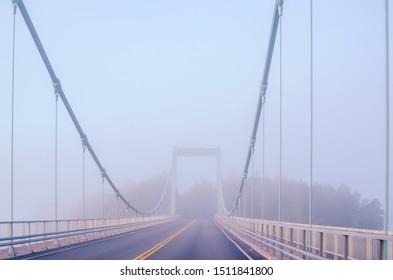 Karisalmi suspension bridge, Paijanne National Park, southern part of Lake Paijanne. Blue lakes, fog, bridge in Finland. Morning foggy landscape