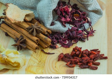 Karkade tea in a sack with spices on a wooden table