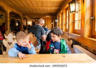 Karkonosze Mountains, Poland - May 9, 2018: Two boys sitting by a empty table of a wooden mountain restaurant waiting for food and drinks