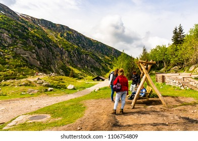 Karkonosze Mountains, Poland - May 9, 2018: Adults and kids by a wooden swing seat next to a mountain footpath on a cloudy day