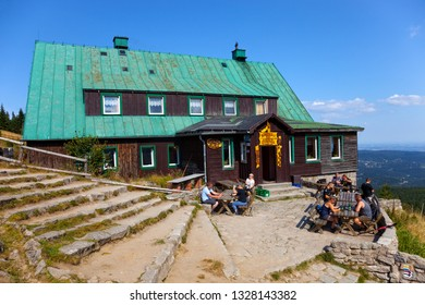 KARKONOSZE, POLAND - AUGUST 17, 2018: Tourists resting in front of wooden shelter Under the Labski Mountains.