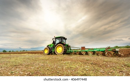 Karlovo, Bulgaria - August 22th, 2015: Ploughing a field with John Deere 7230R tractor. John Deere 8100 was manufactured in 1995-1999 and it has JD 7.6L or 8.1L 6-cyl diesel engine.