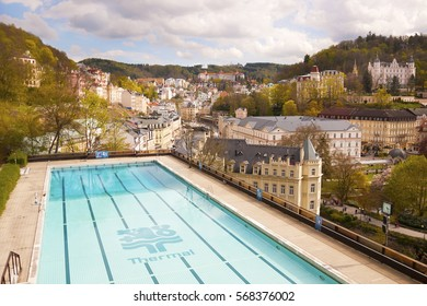 KARLOVY VARY, CZECH REPUBLIC, APRIL 26, 2014: Panoramic view of Carlsbad from hotel Thermal with beautiful large outdoor swimming pool, spa district in Bohemia