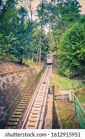 Karlovy Vary, Czech Republic, May 10, 2019: Funicular rails on slope of hill to Diana Observation lookout Tower (Rozhledna Diana), thick dense foliage forest wood near Carlsbad town, West Bohemia