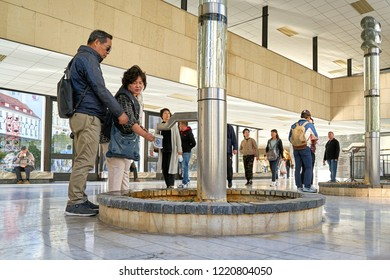 KARLOVY VARY, CZECH REPUBLIC – SEPTEMBER 30, 2018: Tourists on a Fountain in the Thermal Spring Colonnade in the city center of Karlovy Vary in the Czech Republic