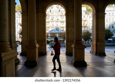 KARLOVY VARY, CZECH REPUBLIC – SEPTEMBER 30, 2018: a tourist walking through the popular Mill Colonnade in the Old Town of Karlovy Vary in the Czech Republic.