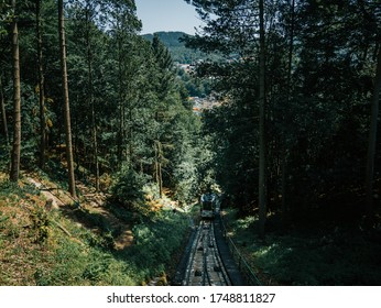KARLOVY VARY (KARLSBAD)/CZECH REPUBLIC-July 28th 2019: Funicular rails on slope of hill to Diana Observation lookout Tower (Rozhledna Diana), thick dense foliage forest wood near Carlsbad town,