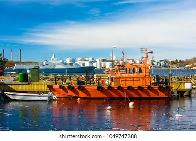 Karlshamn, Sweden - March 19, 2018: Documentary of everyday life and environment. Swedish pilot vessel 218 SE in harbor. Visby class navy corvette vessel K35 Karlstad passing behind.