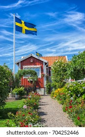 KARLSKRONA, SWEDEN - 2017 July. Typical red Swedish wooden house with national flag in the city of Karlskrona.