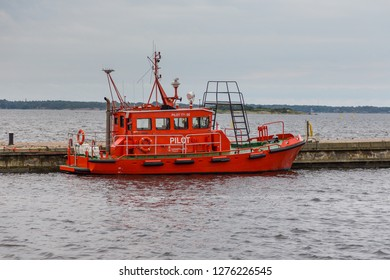 Karlskrona, Sweden- 31 August 2014: Red pilot ship moored in the port of Karlskrona. Water of the bay in the city center.
