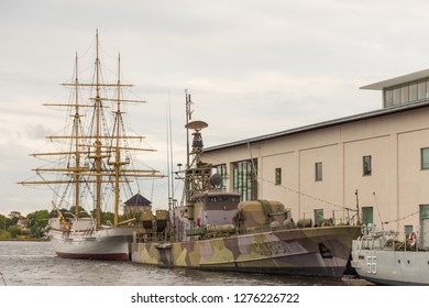 Karlskrona, Sweden - 31 August, 2014: Warships and sailing ship, external Marinmuseum exhibits maritime museum at Stumholmen island. Building museum in the background.