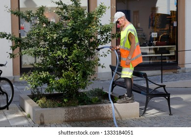 Karlskrona, Sweden - August 23, 2017: A man in work clothes watering plant with tube in urban environment