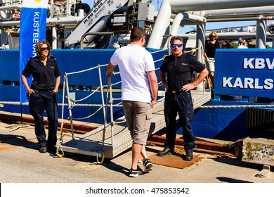 Karlskrona, Sweden - August 27, 2016: Coast guard personnel welcoming visitor to the public open ship day. Vessel in background is KBV 003, a multipurpose ship.
