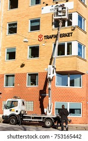 Karlskrona, Sweden - October 30, 2017: Documentary of everyday life and environment. Two workers attaching a sign to high rise building, using truck mounted aerial work platform.
